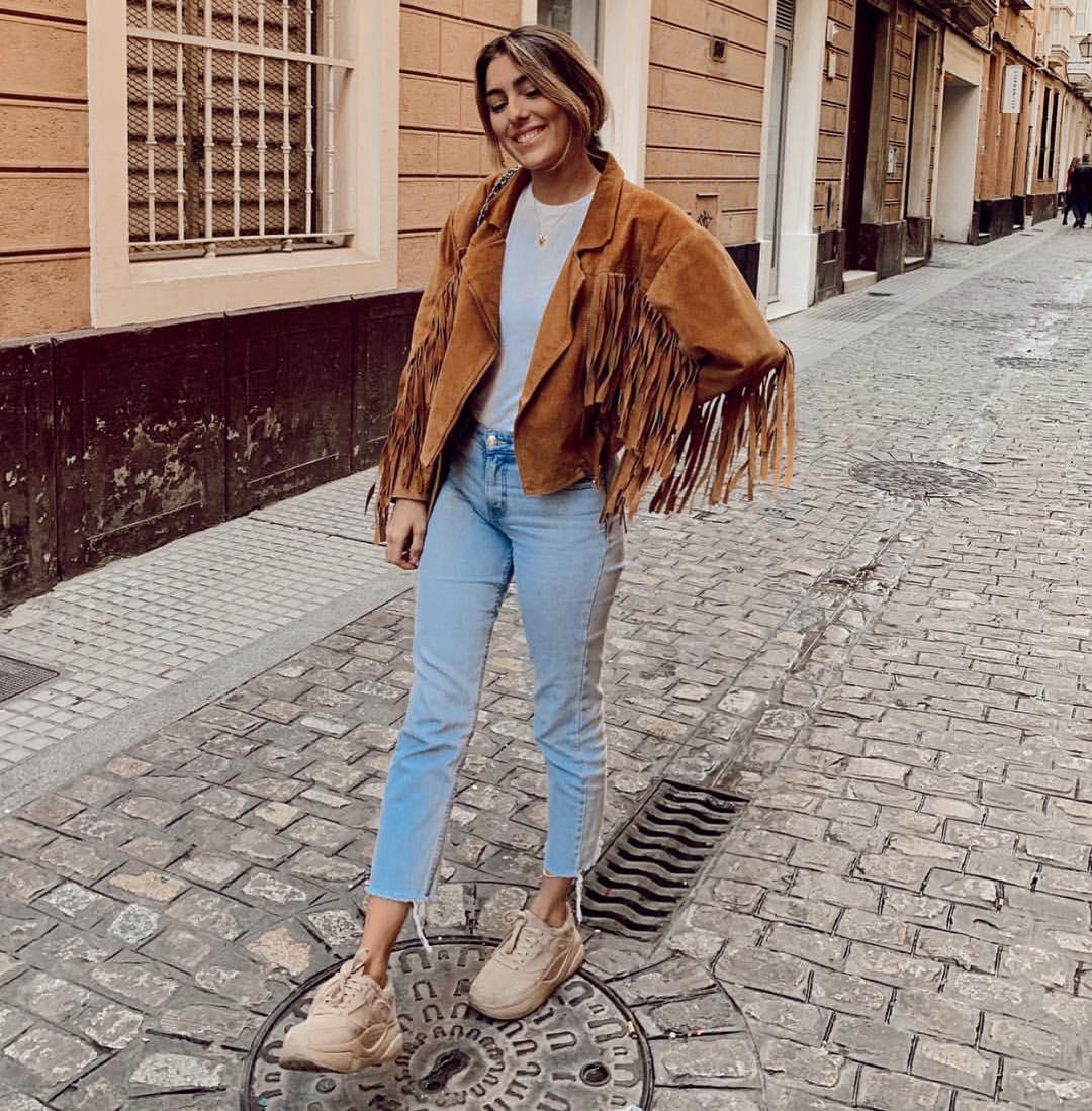 Modelo de Magpie con vaqueros y chaqueta de flecos marrón. Magpie es una tienda de ropa vintage en Madrid.